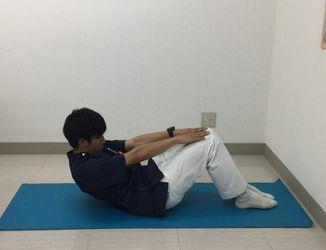 両腕を前方に伸ばし、お臍を覗き込むように息を吐きながらゆっくりと上体を起こすイメージ写真