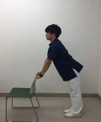 イスの背に手を置き、肩幅に足を開き、背筋を伸ばして立つイメージ写真